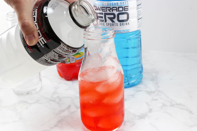 The Patriotic Red, White and Blue Layered Drink Recipe is easy to make. The key is the sugar content in the drinks and to pour them over ice so they don't mix.