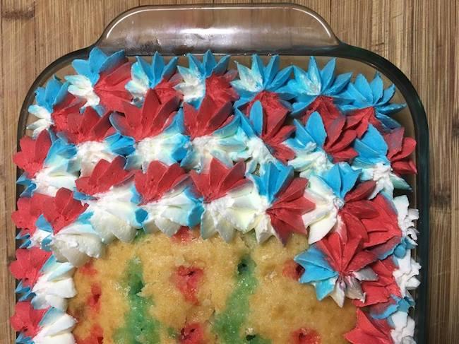 Piping stars on patriotic poke cake