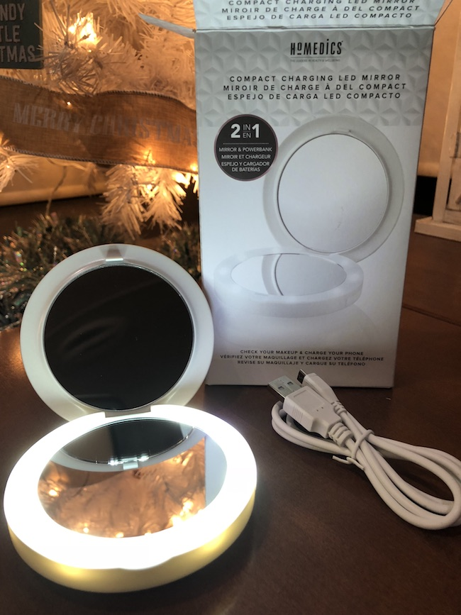 HoMedics Lighted Compact Mirror does dual duty? A phone charging bank and lighted compact makeup mirror all in one. Charges via USB that comes with it.